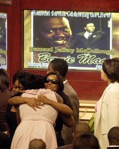 Mourner hugs family member