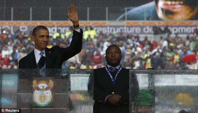 U.S. President Barack Obama addresses the crowd while the 'interpreter' stands next to him