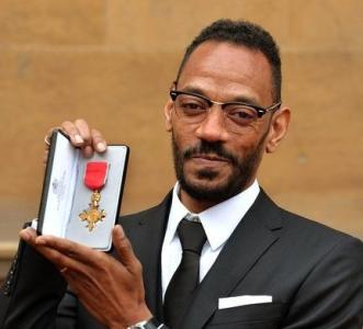 Photograph courtesy of The Voice: Darcus Beese poses with his OBE